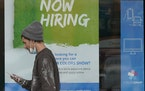 """A man walks past a """"Now Hiring"""" sign on a window at Sherwin Williams store, Friday, Feb. 26, 2021, in Woodmere Village, Ohio."""