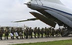 Russian paratroopers load into a plane for airborne drills during maneuvers in Taganrog, Russia, Thursday, April 22, 2021.