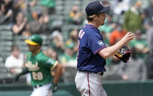 Twins pitcher Kenta Maeda stands on the mound as Oakland's Matt Olson rounds the bases after hitting a solo home run