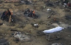 Multiple funeral pyres of patients who died of COVID-19 were burning in a large area converted into a site for mass cremations in New Delhi, India.