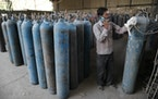 A worker refilled medical oxygen cylinders at a charging station on the outskirts of Prayagraj, India, on Friday, April 23, 2021. India put oxygen tan