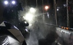 Journalists are hit with pepper spray by law enforcement officers outside the Brooklyn Center Police Department on April 14, the fourth night of unres