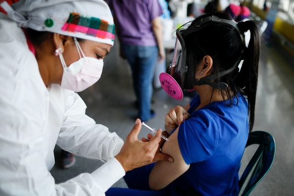 A health care worker inoculated Dr. Virma Rivas with the Sputnik V COVID-19 vaccine on Friday, as part of a vaccination campaign in Tegucigalpa, Hondu
