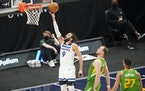 Timberwolves guard Ricky Rubio lays up the ball as Utah guard Joe Ingles, center, defends