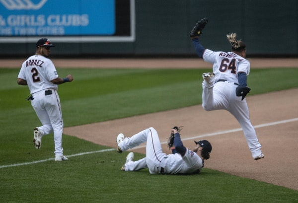 Twins first baseman Willians Astudillo (64) jumped over teammate right fielder Jake Cave (60) after he caught a foul ball hit by Pittsburgh's Erik G