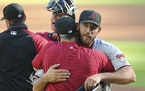 Arizona Diamondbacks starting pitcher Madison Bumgarner gets a hug from manager Torey Lovullo after going the distance over after the seventh inning o