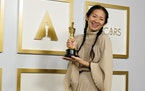 """Director and producer Chloe Zhao, winner of the award for best picture for """"Nomadland,"""" poses in the press room at the Oscars on Sunday, April 25,"""