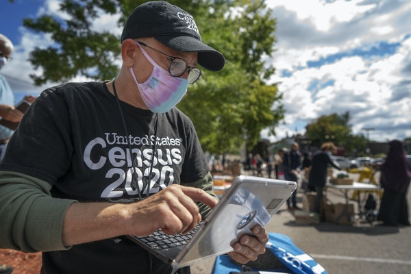 Census worker Daniel Crawford gathered information from a person in the Cedar-Riverside area of Minneapolis last September during a food drive.