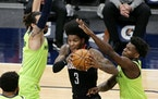 Rockets guard Kevin Porter Jr. tried to escape a double-team by the Wolves' Ricky Rubio (left) and Anthony Edwards when the teams met at Target Cent