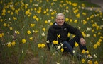 Warren Kapsner with a small portion of the daffodils he planted in his yard last year.