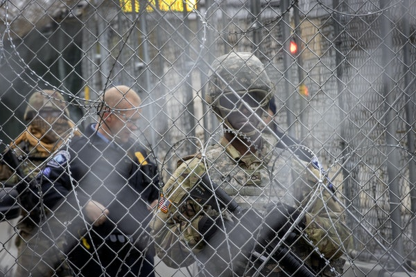 Military and security around downtown Minneapolis watched as protesters marched after the Chauvin case went to the jury on April 19, 2021. ELIZABETH F