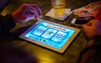 A bar patron plays electronic pulltabs in Coon Rapids.