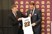 New Gophers men's basketball coach Ben Johnson receives his own number from athletic director Mark Coyle on March 23.