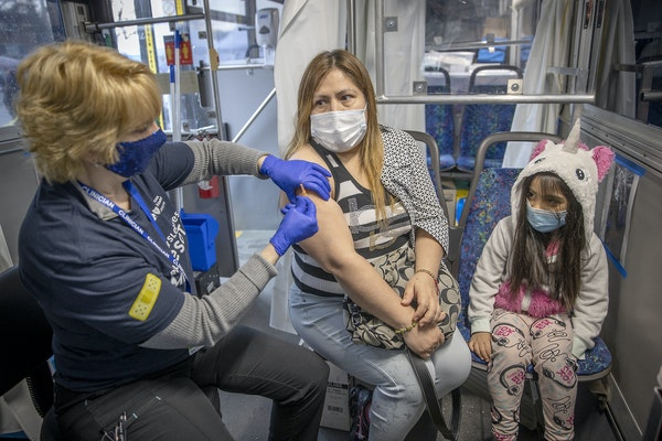Evangelina de Santiago, with her daughter Alyssa Fajardo, received COVID-19 vaccine from nurse Carol Brown at a mobile vaccine clinic Tuesday in Richf