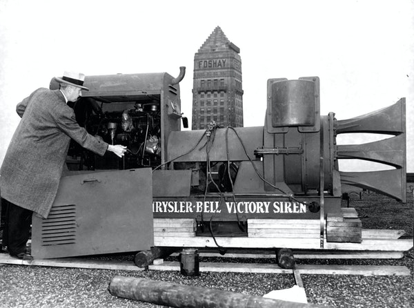 Howard O. Kelly of Minneapolis' Civilian Defense Council inspects the 5,500-pound siren atop the Northwestern National Bank in 1943. This siren prec