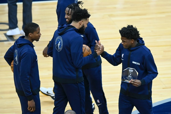 Timberwolves forward Anthony Edwards, right, high-fived center Karl-Anthony Towns after a presentation naming Edwards the Rookie of the Month for Marc