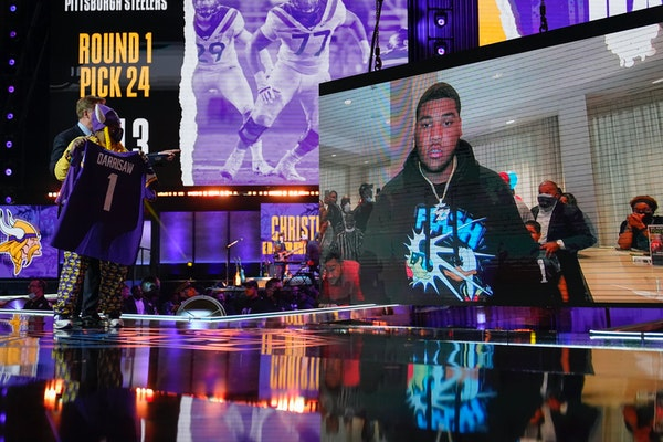 A Minnesota Vikings fan, left, holds a team jersey as an image of Christian Darrisaw is shown on stage at the draft in Cleveland.