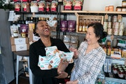 Junita Flowers and Kayla Yang-Best shared a laugh at Seasoned Specialty Food Market in St. Paul, a shop that sells entrepreneurs' small-batch foods.