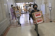 Corenia Smith, campaign manager with Vote Yes 4 Minneapolis, led a group carrying boxes of signed petitions into City Hall on Friday.