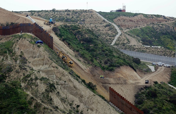 In this March 11, 2019, file photo, construction crews replace a section of the primary wall separating San Diego, above right, and Tijuana, Mexico, b