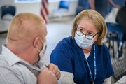 Hennepin Healthcare nurse Christine Runyon talked to Michael Christy after giving him the COVID-19 vaccine at United Labor Center in Minneapolis this