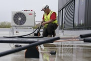 Pipe fitter Brian DeGidio, who works for Wenzel Heating and Air Conditioning in Eagan, hooked up refrigerant lines to air source heat pumps on the roo