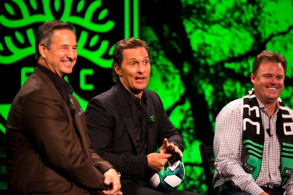 Matthew McConaughey, center, jokes as Dell President and Chief Commercial Officer Marius Haas, left, and Austin FC CEO Anthony Precourt laugh during a