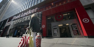 A woman carries Target shopping bags as she leaves the store, Monday, April 19, 2021 in New York.