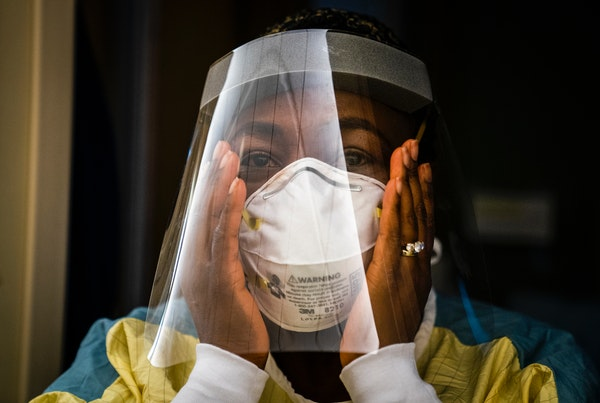 Nurse manager Nkeiru Adoga adjusted her N95 mask while putting on PPE to visit a COVID-19 patient in a stepdown unit at Regions Hospital in St. Paul o