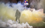 A demonstrator walked amid the tear gas emitted from canisters outside the Brooklyn Center Police Department on April 11, 2021.