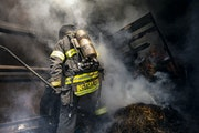 Lake Superior College instructor Dave Werner moved debris around inside a shipping container during a residential fire simulation for recruit training