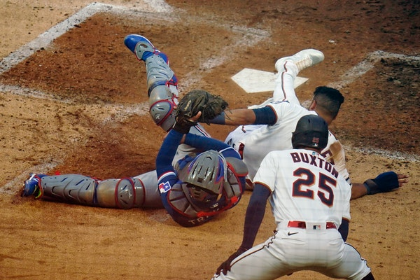 Luis Arraez scrambles back to touch home plate after a collision with Rangers catcher Jose Trevino during the Twins' 6-5 victory on Monday. The play