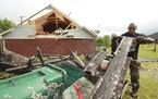Alfred Lee, of Tupelo, cleans up and sorts through the debris in his back yard of his Elvis Presley Drive home on Monday, May 3, 2021 after a tornado