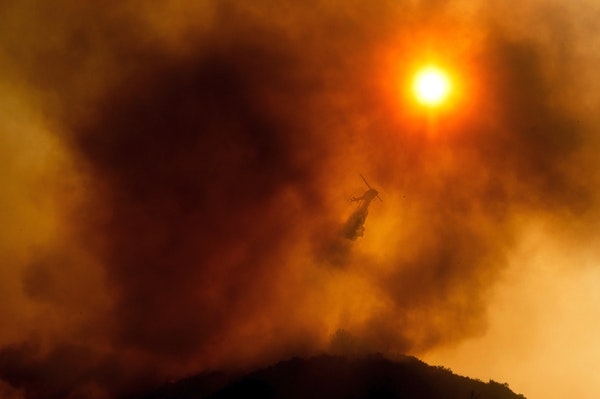 FILE - In this Monday, Aug. 17, 2020 file photo, a helicopter drops water while battling the River Fire in Salinas, Calif. Fire crews across the regio