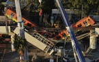 Subway cars dangle at an angle from a collapsed elevated section of the metro, in Mexico City, Tuesday, May 4, 2021. The elevated section collapsed la