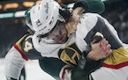 Vegas Golden Knights defenseman Nicolas Hague (14) and Minnesota Wild left wing Marcus Foligno (17) fought each other gloves off in the first period.