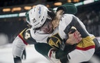 Vegas defenseman Nicolas Hague and Wild winger Marcus Foligno battled during a game this season.
