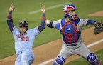 Nelson Cruz (23) of the Minnesota Twins was out at home as Texas Rangers catcher Jose Trevino threw to first in the fourth inning.