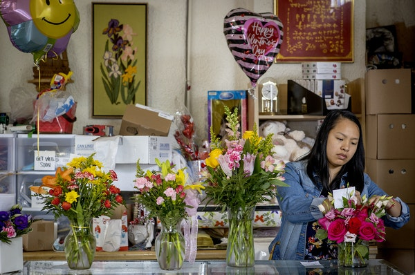 Cara Dalton prepared early Mother's Day orders at Flowers by Miss Bertha, which her parents have owned since 1990.