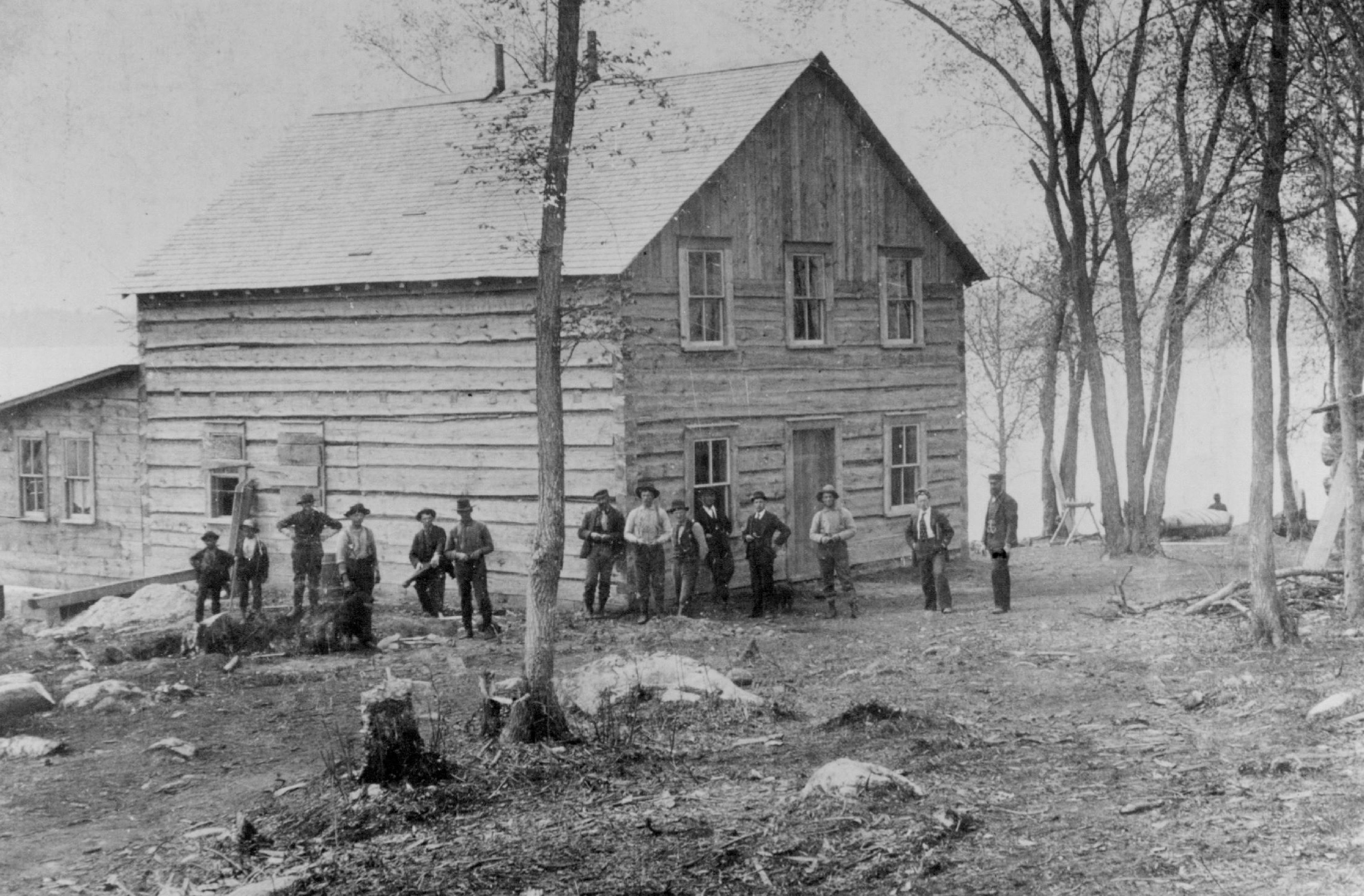 People stand outside the The Green Tree Hotel at Rainy Lake during the gold rush there in the late 1800s.