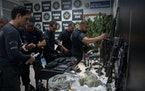 Police officers organize drugs and weapons seized during a police operation against alleged drug traffickers at the Jacarezinho favela in Rio de Janei