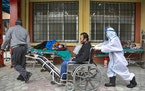 A COVID-19 patient arrives on a wheelchair as others are lying down on beds outside an emergency ward of a government run hospital in Kathmandu, Nepal