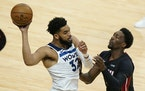 Wolves center Karl-Anthony Towns looked for an open teammate past Heat center Bam Adebayo during the first half.