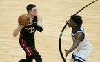 Miami Heat guard Tyler Herro (14) looks for an open teammate past Minnesota Timberwolves guard Anthony Edwards