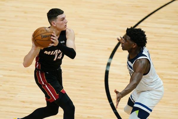 Miami Heat guard Tyler Herro (14) looks for an open teammate past Minnesota Timberwolves guard Anthony Edwards