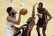 Timberwolves center Karl-Anthony Towns, left, goes up for a shot against Miami forward Trevor Ariza (8) as guard Kendrick Nunn (25) looks on during th
