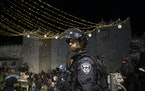 An Israeli police officer stands guard at the Damascus Gate to the Old City of Jerusalem after clashes at the Al-Aqsa Mosque compound, Friday, May 7,