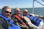 (Above) Paul Bower, flanked by Jim Tuller, left,  and James Powers mark their calendars to hit the lake on the Saturday after the state fishing opener