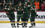 Minnesota Wild center Victor Rask, defenseman Jared Spurgeon, left wing Kevin Fiala and left wing Kirill Kaprizov, from left, celebrate after Spurgeo