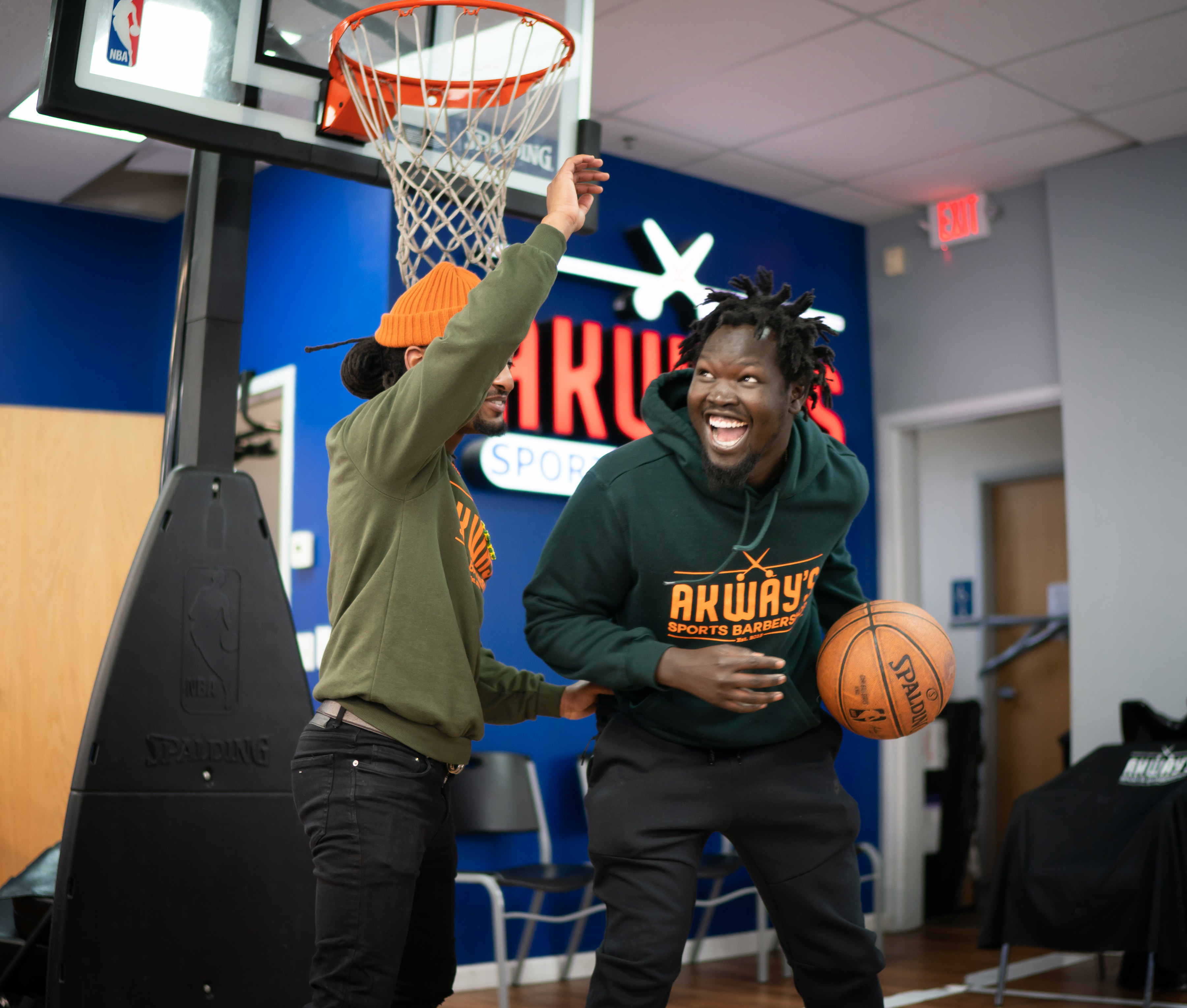 Akeem Akway, right, shoots hoops during some down time at their barbershop with cousin and business partner, Nathan Sheferaw.